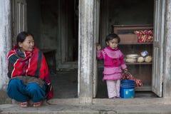 有她的女儿的一名妇女在Panauti,尼泊尔 免版税库存图片
