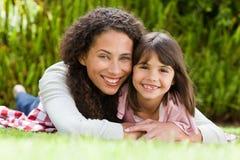 有她的女儿的可爱的母亲在庭院里 库存图片