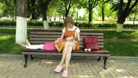 有她的女儿的妈妈,说谎在一年轻女人的膝部的学龄前女孩在长凳的公园 r 影视素材