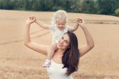 有她的女儿的少妇在sunn的一块麦田的 库存图片