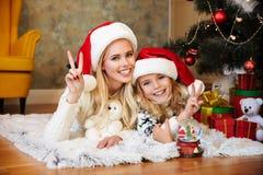有她的女儿的年轻微笑的母亲圣诞老人看的` s帽子的 免版税库存图片