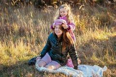 有她的女儿的年轻美丽的母亲步行的在一晴朗的秋天天 女儿在母亲上设法把她的帽子放,他们是la 库存图片