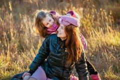 有她的女儿的年轻美丽的母亲步行的在一晴朗的秋天天 女儿在母亲上设法把她的帽子放,他们看起来  免版税库存图片