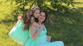 有她的女儿的怀孕的女孩礼服的在公园 股票视频