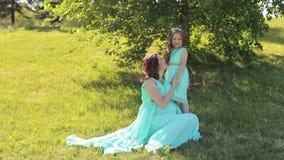 有她的女儿的怀孕的女孩礼服的在公园 股票录像