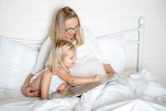 有她的女儿的怀孕的年轻母亲 免版税图库摄影