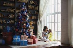 有她的女儿的怀孕的母亲在圣诞树附近 库存图片