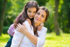 有她的女儿的愉快的年轻母亲 图库摄影