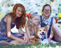 有她的女儿的母亲和狗坐草 免版税库存照片