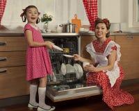 有她的女儿的母亲在厨房里 免版税库存照片