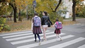 有她的女儿的母亲秋天的在学校以后回家并且在行人穿越道穿过路 股票视频