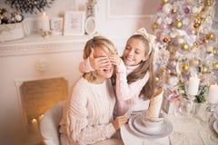 有她的女儿的美丽的年轻母亲新年的内部的在圣诞树附近的桌上 免版税库存照片