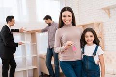 有她的女儿的美丽的母亲把握与钥匙圈的关键以房子的形式 免版税库存照片
