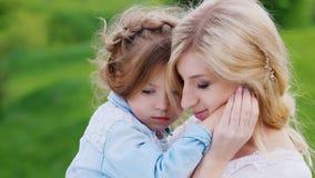 有她的女儿的美妙地加工好的母亲轻轻地拥抱以绿色叶子为背景 股票视频