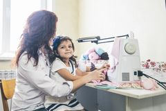 有她的女儿的裁缝年轻美丽的妇女缝合与缝合 库存图片