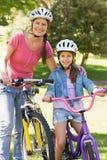 有她的女儿骑马自行车的妇女 免版税库存照片