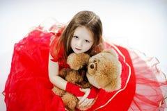 有她的女用连杉衬裤熊玩具朋友的逗人喜爱的小女孩 免版税库存照片