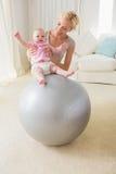 有她的女婴的愉快的母亲exercice球的 免版税库存照片