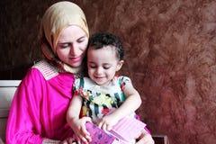 有她的女婴的愉快的阿拉伯回教母亲 库存图片