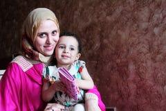 有她的女婴的愉快的阿拉伯回教母亲 图库摄影