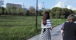 有她的妈妈的年轻母亲在公园 影视素材