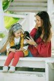 有她的妈妈的愉快的微笑的儿童女孩穿有约克夏狗逗人喜爱的小狗的时尚温暖的衣裳户外 库存图片