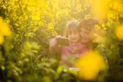 有她的妈妈的愉快的逗人喜爱的女孩夏天领域的 免版税库存图片
