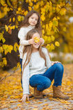 有她的妹妹的逗人喜爱的女孩在秋天公园 免版税库存照片