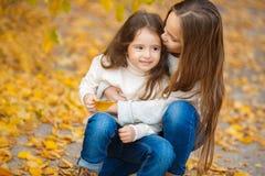有她的妹妹的逗人喜爱的女孩在秋天公园 免版税库存图片