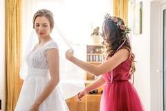 有她的婚礼面纱的女傧相帮助的新娘 免版税库存照片