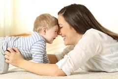 有她的婴孩的富感情的母亲 库存照片