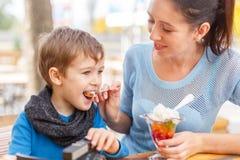 有她的婴孩的愉快的年轻母亲室外咖啡馆的 库存照片