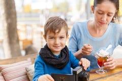 有她的婴孩的愉快的年轻母亲室外咖啡馆的 免版税库存照片