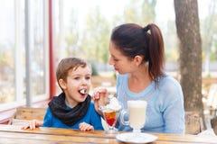 有她的婴孩的愉快的年轻母亲室外咖啡馆的 库存图片