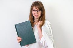 有她的学术论文工作的愉快的毕业生妇女在白色 库存图片