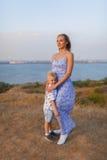 有她的孩子的一位惊人的女性在自然本底 愉快的系列一起 母性和童年 免版税库存照片