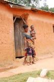 有她的孩子的一名未认出的非洲妇女门阶的 库存图片