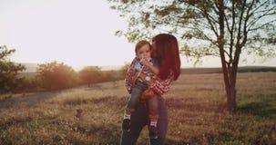 有她的孩子的微笑的年轻母亲领域中部的,在拥抱和亲吻她的婴孩的日落,婴孩吃a 股票录像