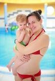 有她的孩子的怀孕的母亲游泳池的 免版税图库摄影