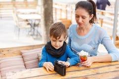 有她的孩子的愉快的年轻母亲一个室外咖啡馆的 库存照片
