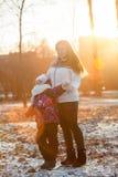 有她的孩子的母亲步行的在冬天公园,晚上,日落 图库摄影