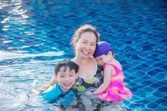 有她的孩子的母亲游泳池的 图库摄影