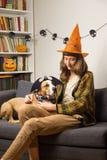 有她的宠物的年轻女性在沙发在客厅为万圣夜党穿戴了 图库摄影