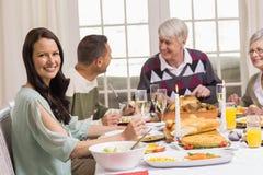 有她的家庭的微笑的妇女在圣诞晚餐期间 库存图片
