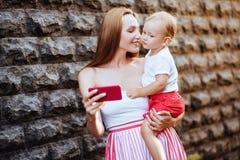 有她的小儿子的年轻母亲在城市 免版税库存图片
