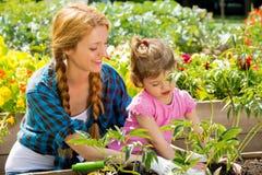 有她的小女儿的妇女在庭院里 免版税库存图片