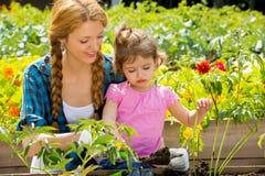 有她的小女儿的妇女在庭院里 图库摄影