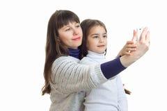 有她的小女儿的妈妈在电话和微笑做照片 免版税库存照片