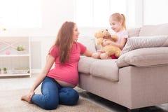 有她的小女儿的母亲坐沙发 免版税库存图片