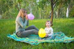 有她的小女儿的年轻母亲吹色的balloo 免版税库存图片